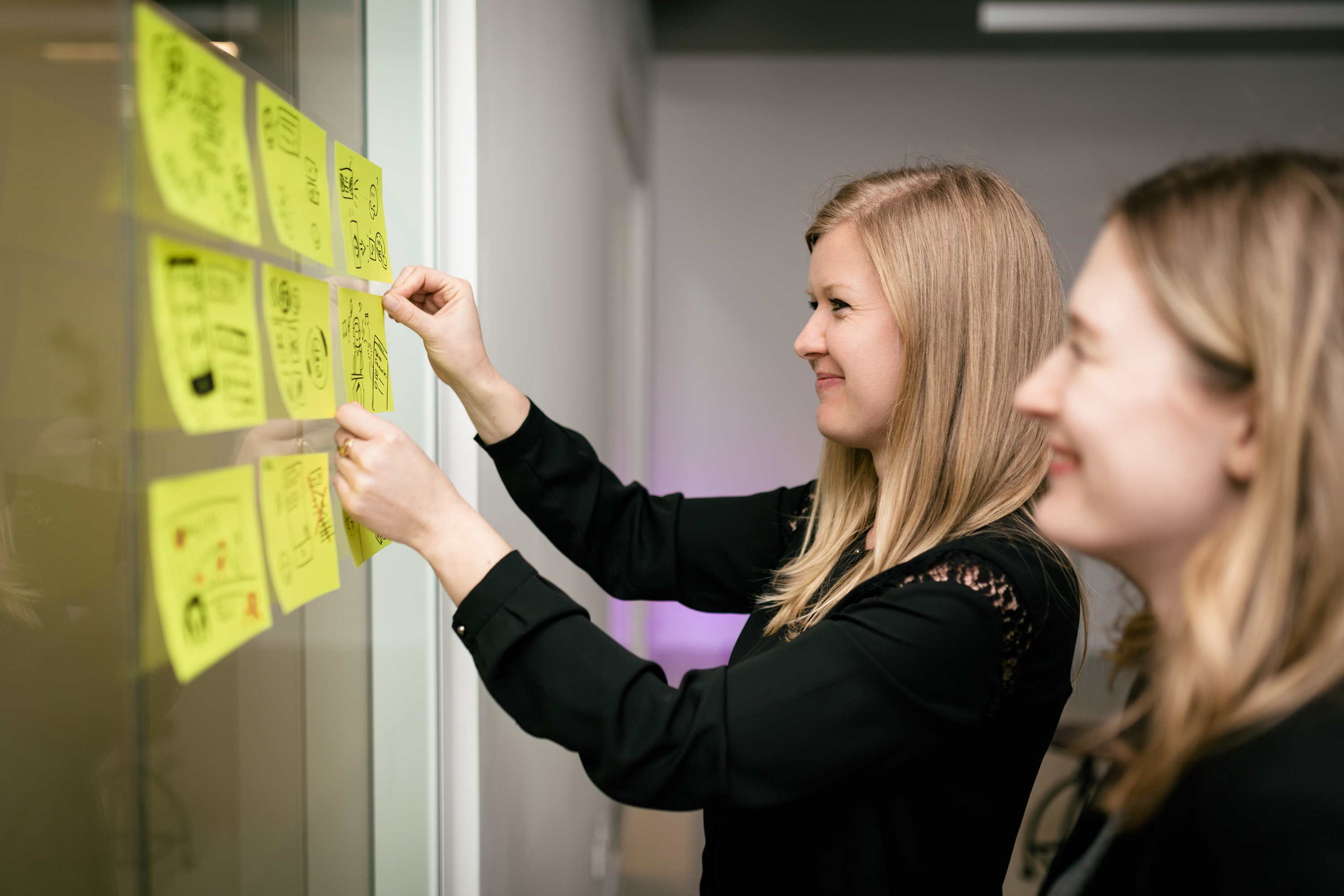 Two people having putting post its on wall during a Design Thinking meeting