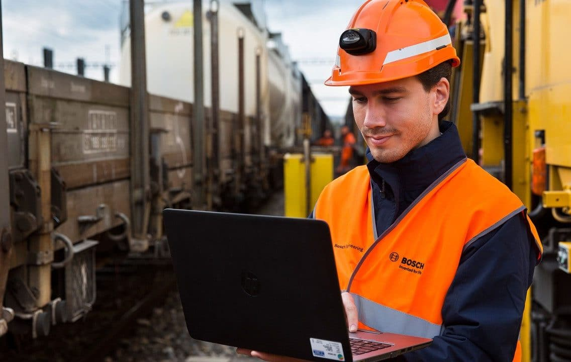 Worker standing between freight trains looking at his laptop.