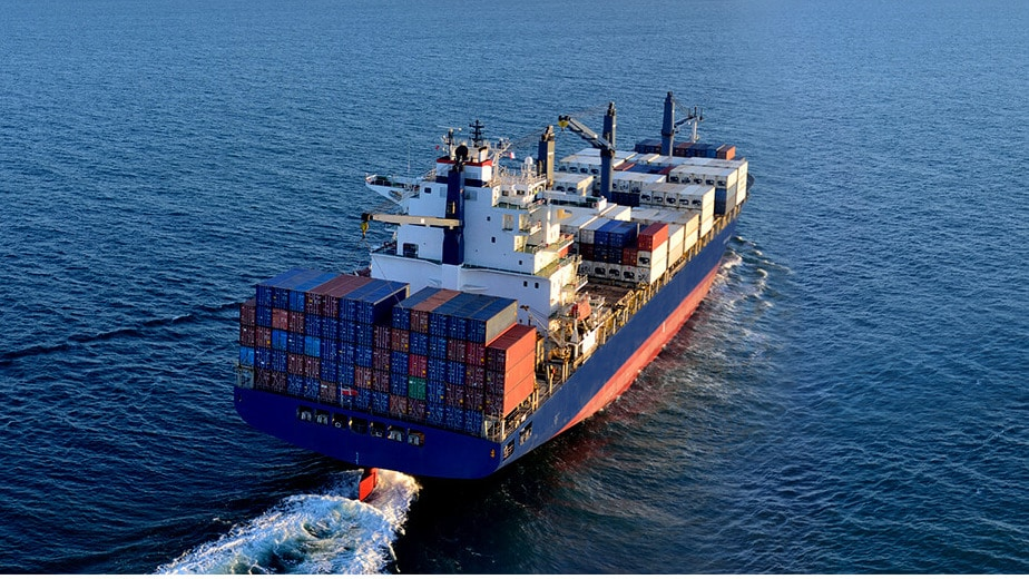 Freight ship on the ocean. A device management tool is used to monitor the goods remotely.