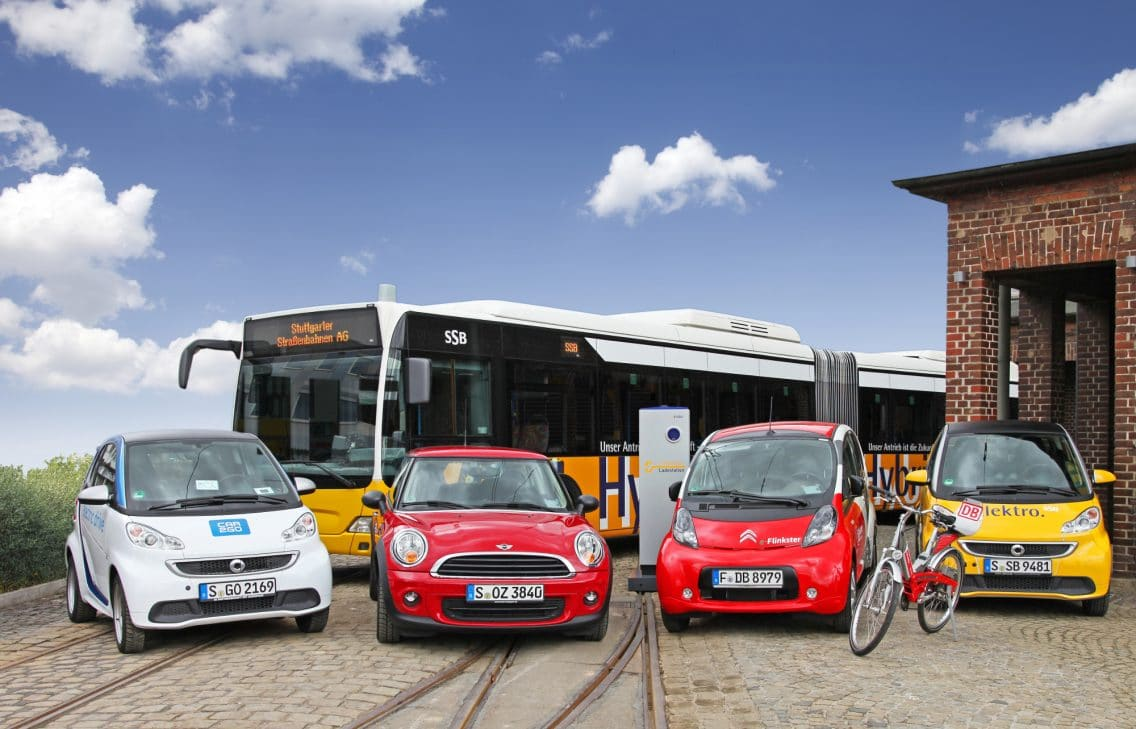 Four cars and a bicycle parked in front of a public bus.