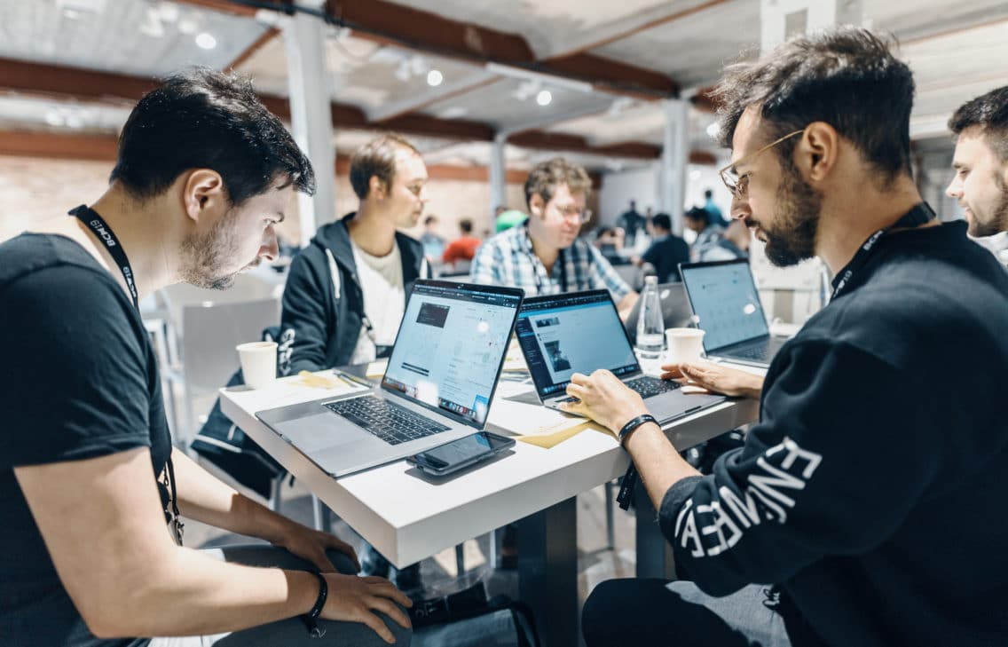 Developers sitting at a table looking at their computers.
