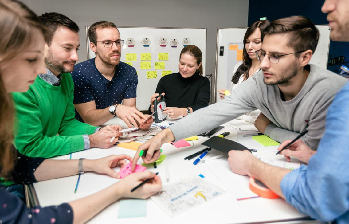 People working together in a design thinking and UX workshop.