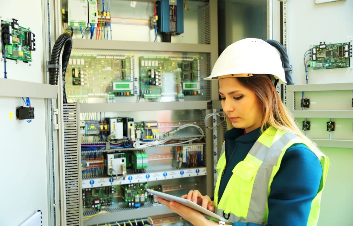 Woman electrician standing in font of a breaker box with a tablet computer in hand.