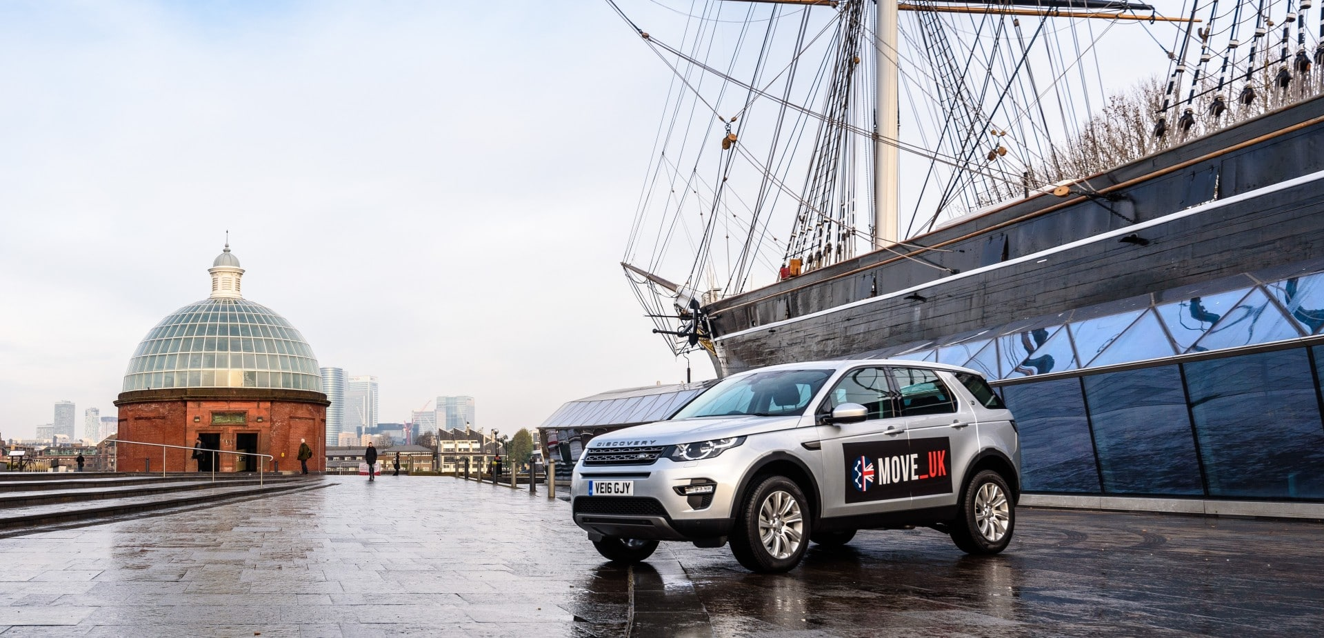 Car labeled Move_Uk in front of a large ship