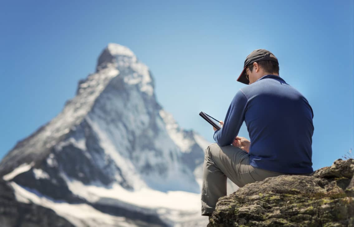 Hiker reading on his digital tablet in the mountains.