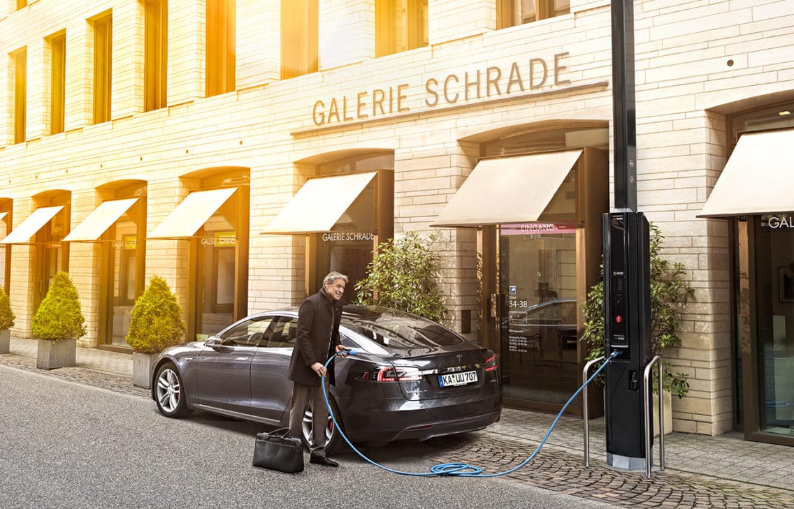 Man charging his electric car at a SMIGHT smart city light with an integrated charging station.