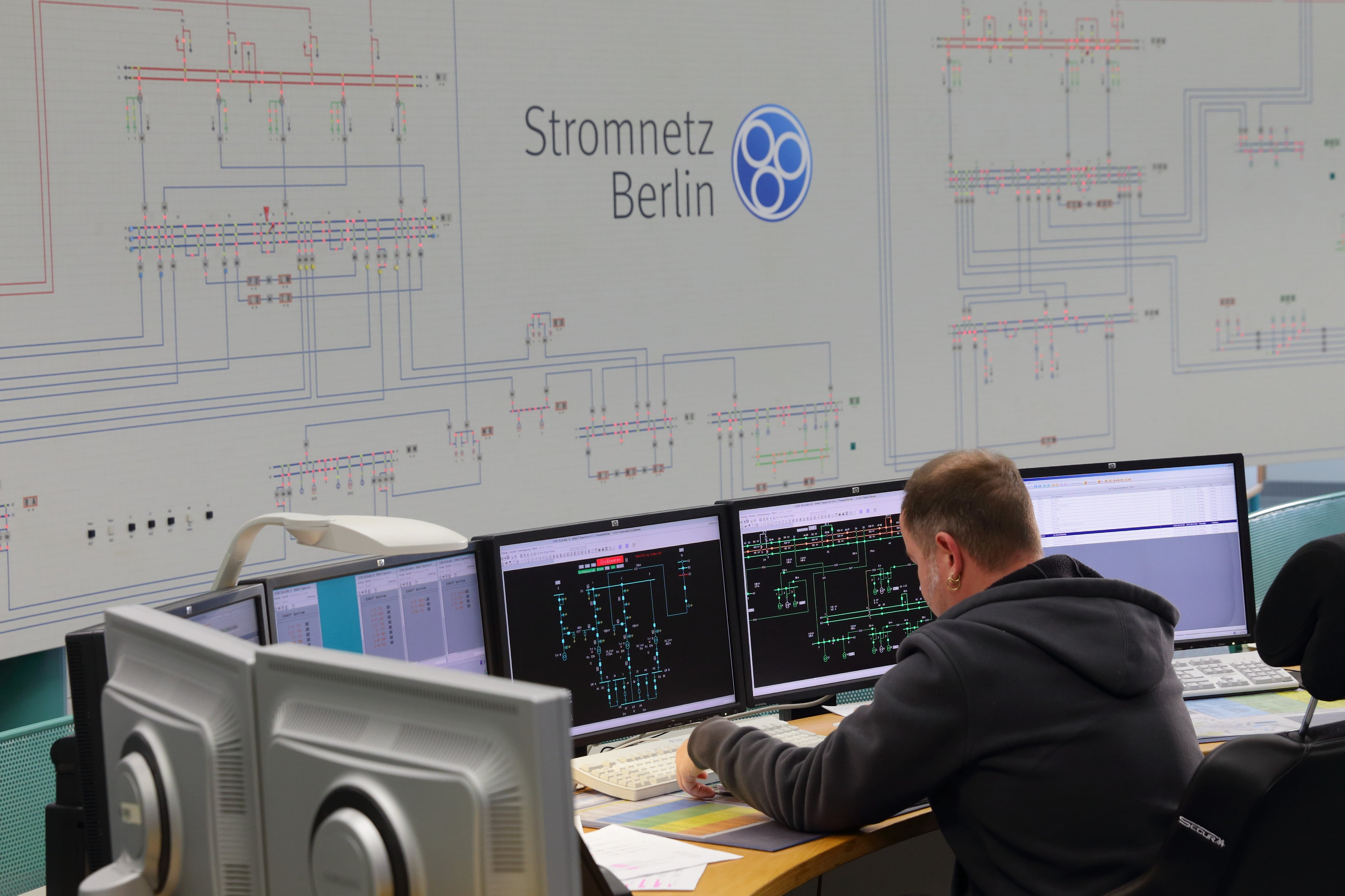 This pictures shows a member of the Stromnetz Berlin staff in the control room, looking at monitors.