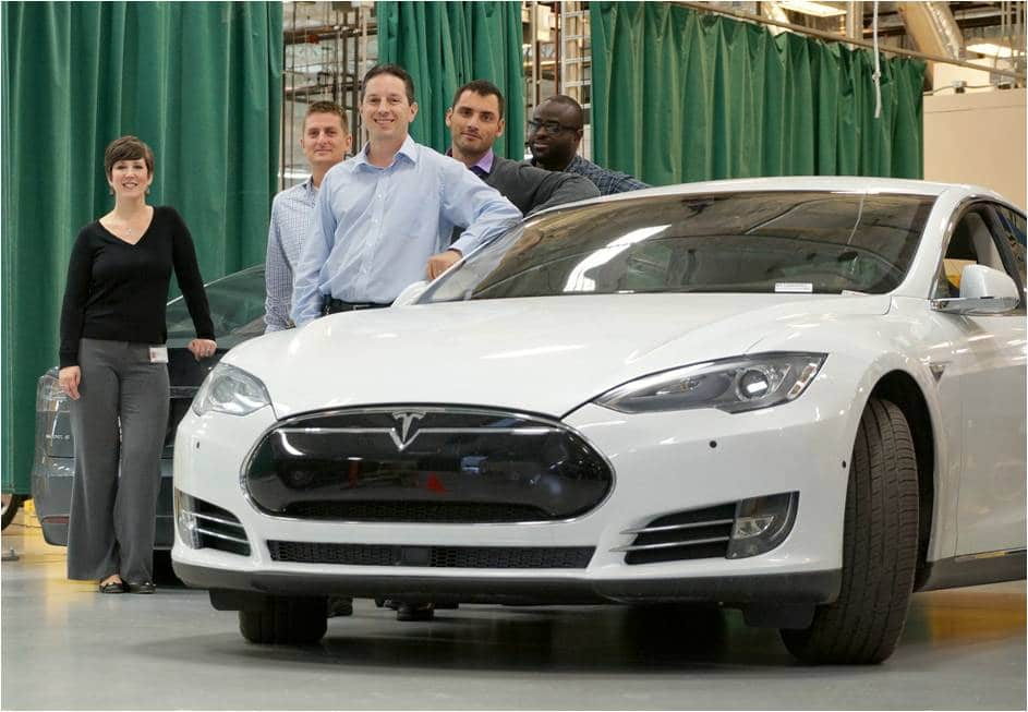 Proud employees next to a Tesla electric vehicle Model S